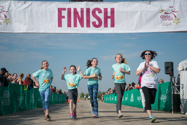 A group of girls celebrates at the finish of the Girls on the Run Chicago Southwest 5.