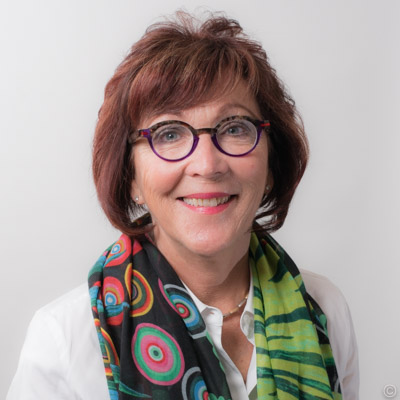 Susan's headshot with a colorful patterned scarf.
