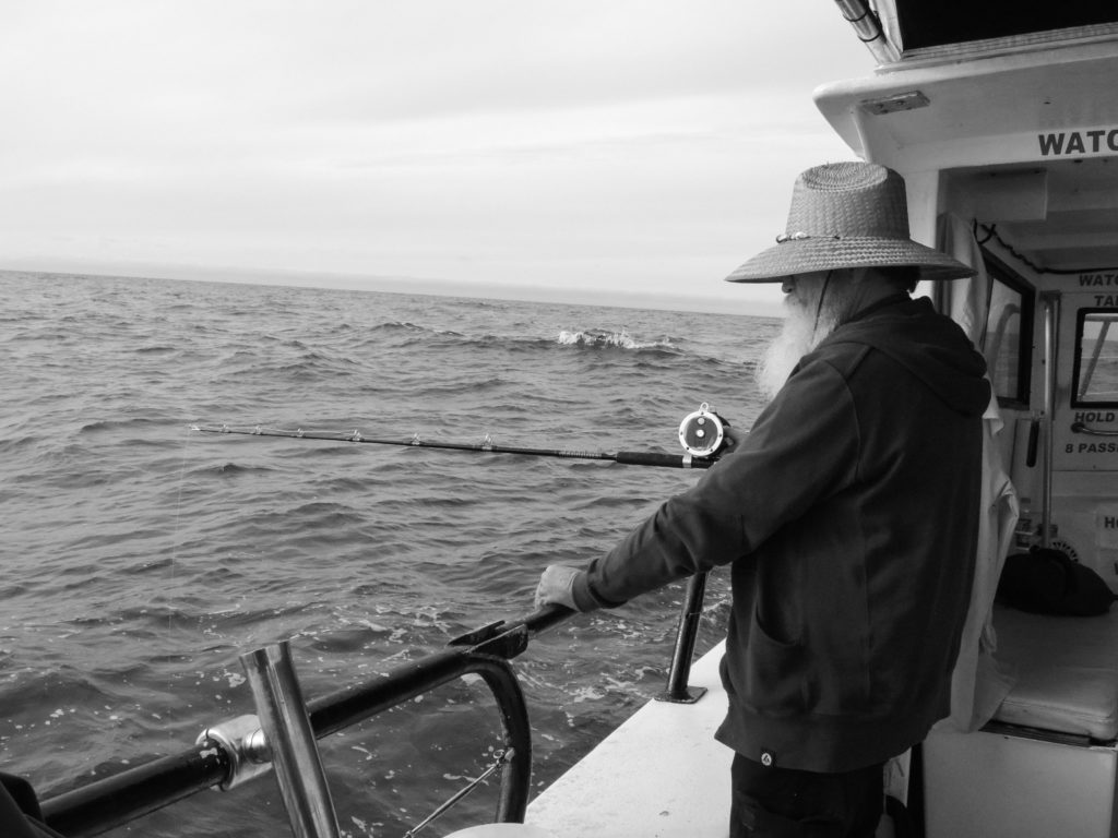 old man fishing on the sea with a rod